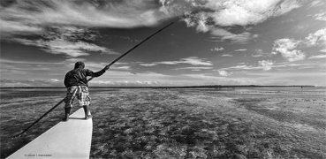 A black and white picture with someone fishing